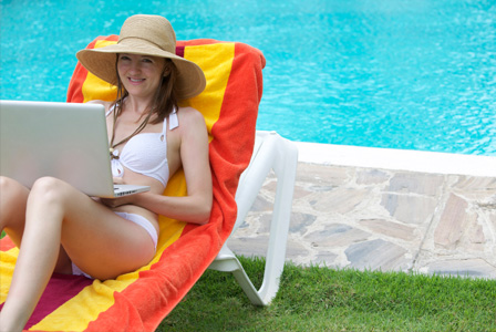 Woman working from home in front of pool