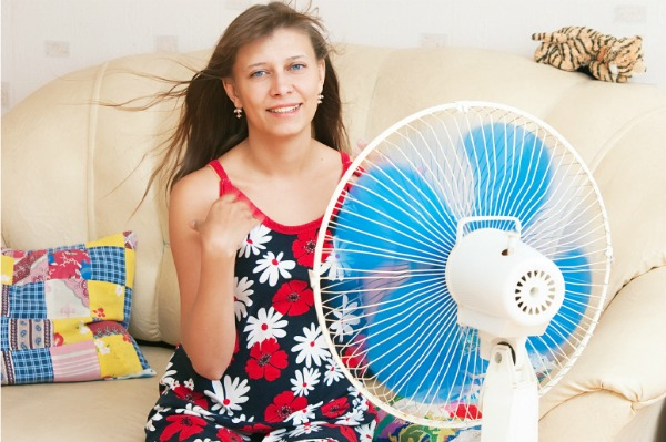 girl cooling off by sitting next ot an oscillating fan