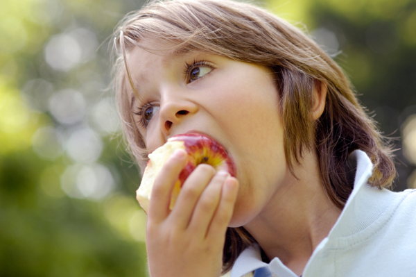boy snacking on an apple after school