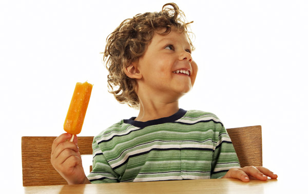 young boy eating popsicle at table