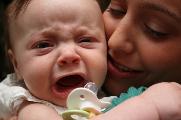 Crying baby with tired mom