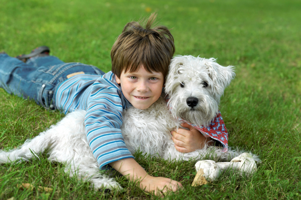 little boy cuddling with dog