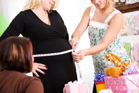 Measuring pregnant belly at baby shower