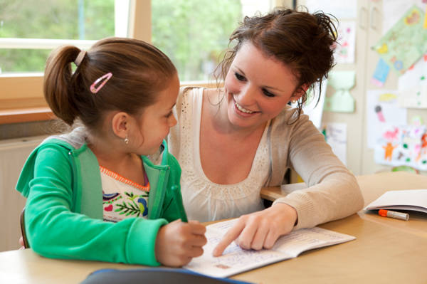 mom working with young daughter to learn