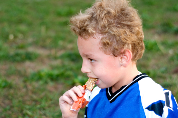 boy eating granola bar on the go