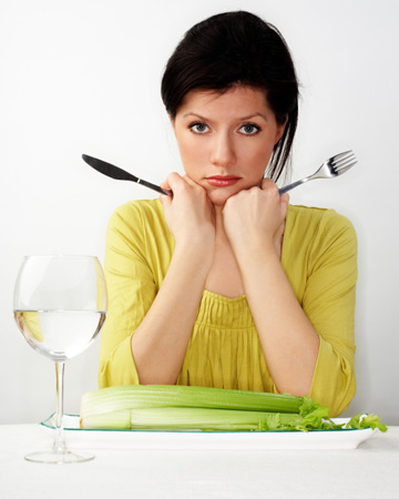 Unhappy woman eating celery