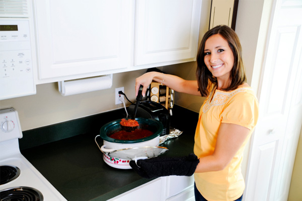 woman preparing dinner in crockpot