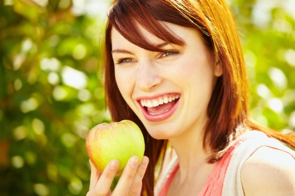 woman snacking on apple