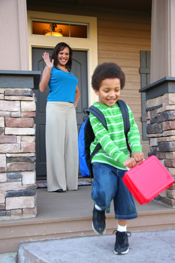 Child with lunch box leaving home