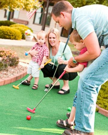 Family playing mini golf