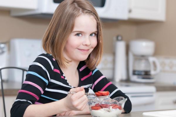 youn girl eating yogurt