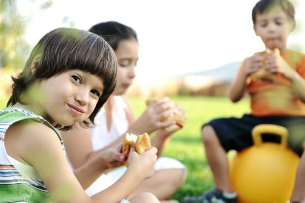 kid eating sandwich outside