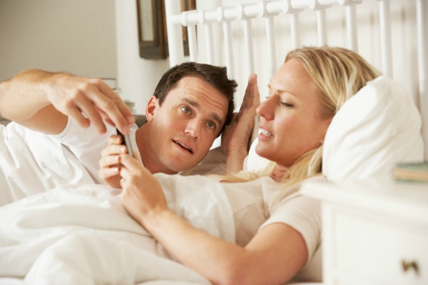 woman on phone in bed with an irritated husband