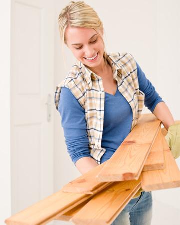 Woman installing wood flooring