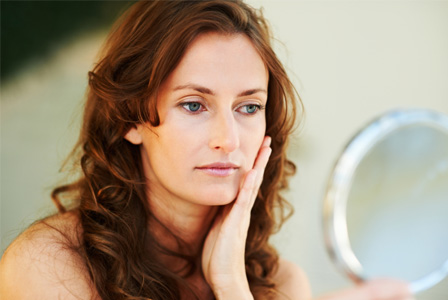 Aging woman looking in mirror