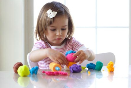 Little girl playing with playdough