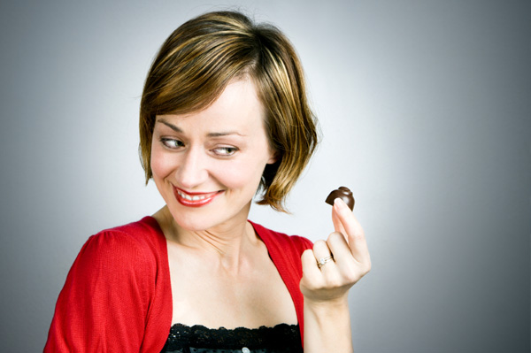 happy woman eating dark chocolate