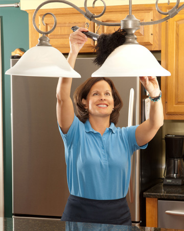 Maid cleaning lighting fixtures