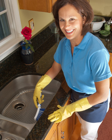 Maid cleaning sink