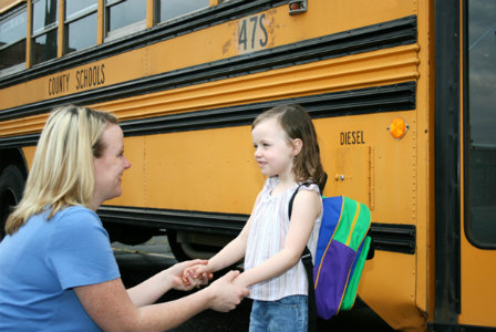 Mother with daughter at school bus