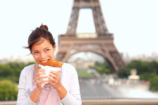 Woman eating in front of Eiffel Tower