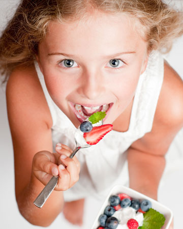 Child eating yogurt and fruit