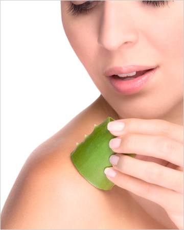 Woman applying aloe vera gel to skkin