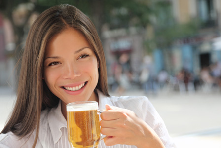 Woman drinking beer outside