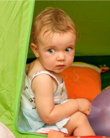baby girl camping on beach