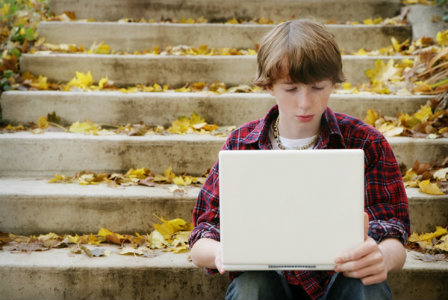 Boy on the computer outdoors
