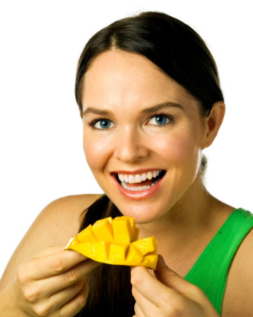 Happy woman eating mango