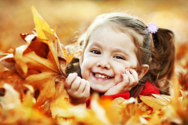 Little girl in fall leaves