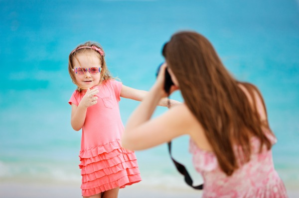 mother photographing daughter on beach vacation
