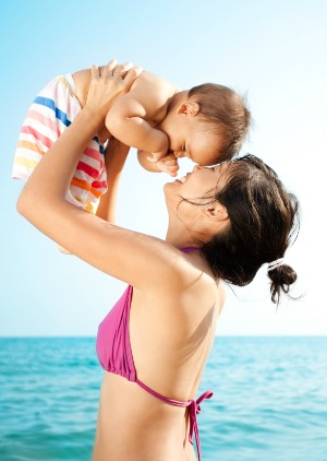 mother holding baby up at beach
