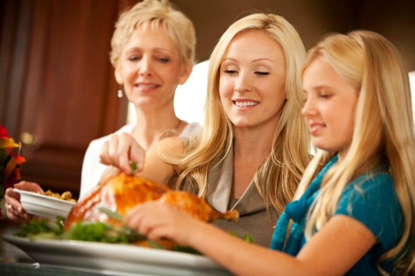 Grandmother, mother and daughter prepping turkey