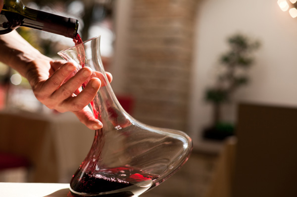 Waiter pouring wine into decanter