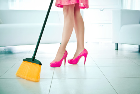 Woman cleaning floor with broom