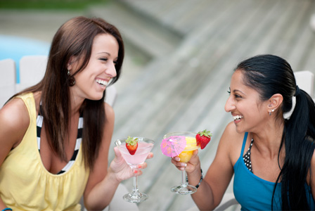 Women having cocktails by the pool