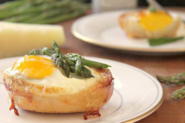 Baked eggs in bread bowls with cheese and asparagus