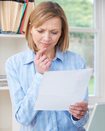 Concerned woman looking at paperwork