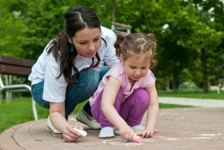 mom doing sidewalk chalk with child