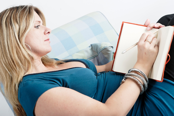 pregnant woman writing in her journal