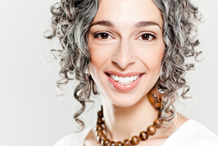 Woman in her 30s with gray hair and nose ring