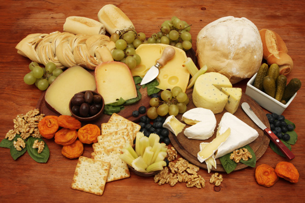 large cheeseboard with fruit nuts olives bread