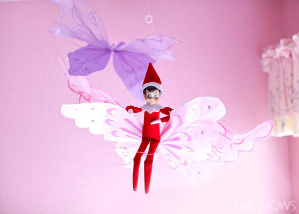 Elf on the Shelf idea 2: Elfie Rojo sitting on a butterfly decoration