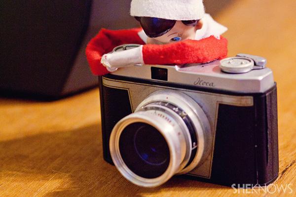 Elf on the Shelf idea 23: Elfie Rojo taking photographs