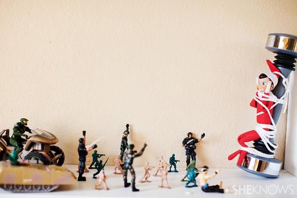 Elf on the Shelf idea 26: Elfie Rojo is captured by Army men
