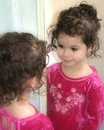 Little girl looking in the mirror