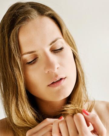 Woman examing hair