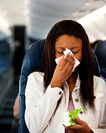 Woman sneezing on plane